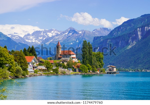 Panoramic view to the Brienz town on lake Brienz by Interlaken, Switzerland. Old fishing town with beautiful church and snow covered Alps mountains on background. Switzerland, Europe.