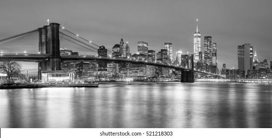 Panoramic view of  Brooklyn Bridge and Lower Manhattan skyline in New York City at night with city illumination, USA. Black and white toned