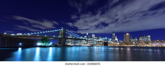 Panoramic view of Brooklyn Bridge and New York City skyline at night