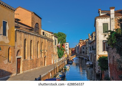 Panoramic view of buildings, bridge and boats in front of a canal at the sunset, in the city center of Venice, the historic and amazing marine city. Located in the Veneto region, northern Italy