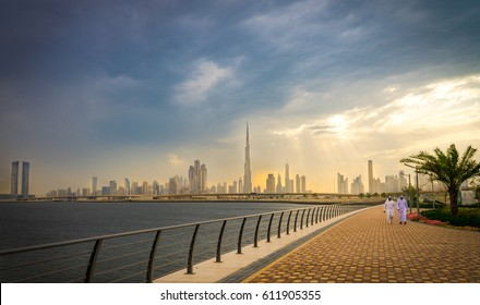 Panoramic view of business bay, downtown area of Dubai and two arab men take a walk on the promenade at cloudy day. UAE