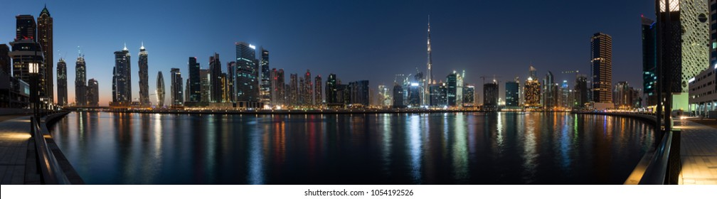 Panoramic view of Business bay skyline with reflection in the water at night, Dubai, UAE