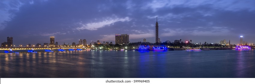 Panoramic view of Cairo city center at twilight, the Kasr El Nile Bridge and the island of Zamalek with its colorful boats on the Nile river.