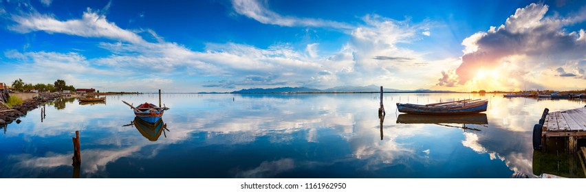 Panoramic view of calm lagoon at sunset with typical fisherman boats and perfect water reflections