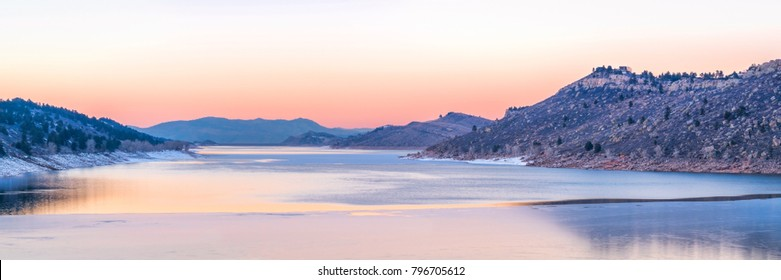 panoramic view of a calm winter dusk over partially frozen Horsetooth Reservoir near Fort Collins in northern Colorado