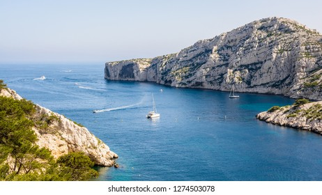 Panoramic view of the cap Morgiou on the mediterranean shore near Marseille, France, with motorboats cruising and sailboats mooring in the blue waters of the calanque de Morgiou on a sunny day.