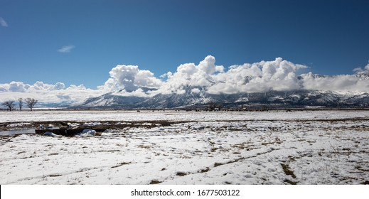 Panoramic view of Carson Valley in Northern Nevada with snow covered mountains and dramatic clouds.