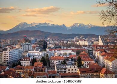 Panoramic view from castle over old town Ljubljana with sunset to mountain range Kamnik–Savinja Alps in Slowenia, Europe