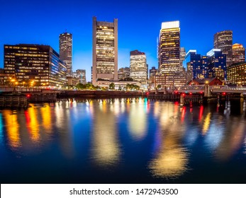 Panoramic view of the city of Boston in Massachusetts, USA at night showcasing its mix of contemporary and historic architecture by Seaport Boulevard.