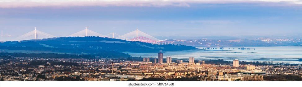 Panoramic view of the City of Edinburgh with the Firth of Forth and the Forth Bridges - including the new Queensferry Crossing - at the background at sunrise. Edinburgh, Scotland, United Kingdom