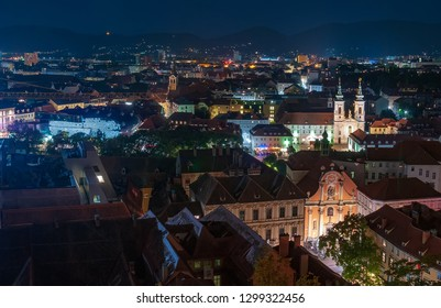 Panoramic view of the city of Graz, Austria at night. Illuminated facades of Trinity Church and Mariahilfkirche. Historic Centre of Graz is inscripted into the UNESCO World Heritage Site list