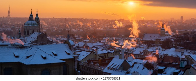 Panoramic view of the city of Prague in winter. Beautiful sunrise over the snow covered roof ot the medieval town.