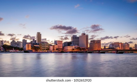 Panoramic view of the city of Recife in Pernambuco, Brazil showcasing its mix of historic and contemporary architecture at sunset by the Capibaribe river.