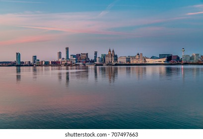 Panoramic view of the city skyline across the Mersey at sunset, with pink and turquoise sky and the buildings reflecting in the water