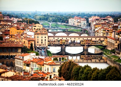 A panoramic view of the cityscape and bridges over the Arno River in Florence, Italy. Tilt-shift blur effect with unrecognizable people.