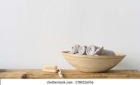 Panoramic view of clean and fresh rolled towels in wooden bowl standing on bench near soft nail brush in bathroom or spa salon. Beauty elements on table against white coy space wall