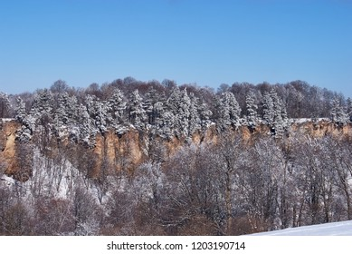 Panoramic view of the cliffs. In the foreground a snowy forest, in the background - blue sky. Lago-Naki, The Main Caucasian Ridge, Russia