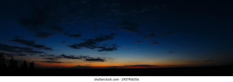 Panoramic view of the clouds in the sky after sunset. Evening twilight in summer.