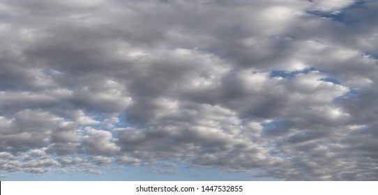 Panoramic View Of Clouds With A Smattering Of Blue Sky Peeking Through From Behind