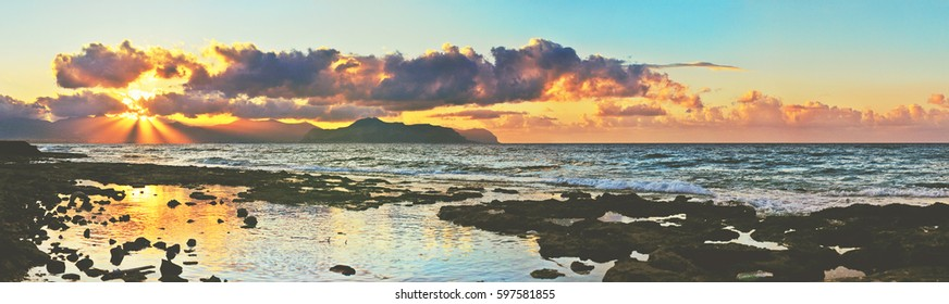 Panoramic view from the coast of Sicily with a stones on foreground, cloudy colorful sunset sky and mountains on background