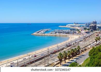 Panoramic view of coast of Tarragona, beach in La Pineda in sunny day with railway tracks along coastline and port with ships and yachts, Tarragona, Catalunya, Spain