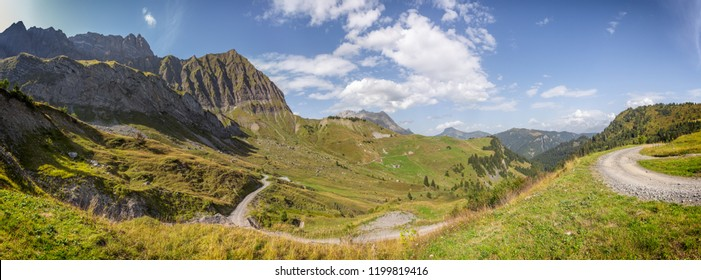 Panoramic view of the Col des Aravis in the French Alps. A dort road is going downhill toward the valley