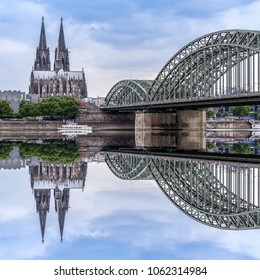 Panoramic view of Cologne Cathedral and Hohenzollern Bridge with its reflection, Cologne, Germany.