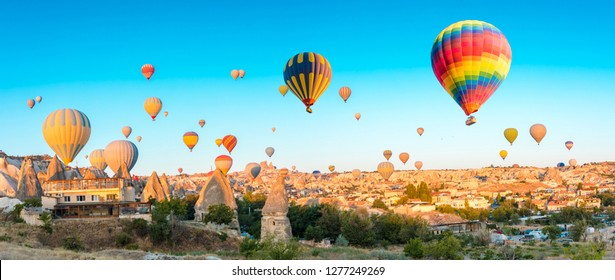 Panoramic view of Colorful hot air balloons flying over at fairy chimneys in Nevsehir, Goreme, Cappadocia Turkey. Hot air balloon flight at spectacular Cappadocia Turkey.