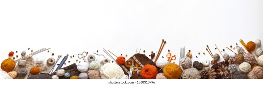 Panoramic view of composition with knitting accessories: balls of wool yarn, set of knitting needles, hooks, and other knit tools on white background. Long banner, top view, copy space, flat lay