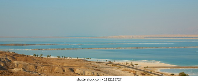 Panoramic view of the dead sea leaving in the horizon with salt-covered banks, Israel