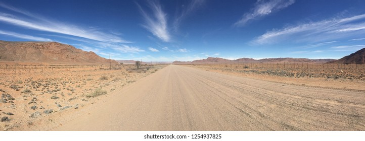 Panoramic view of a dirt or gravel road in the rugged arid terrain of rural Namibia.