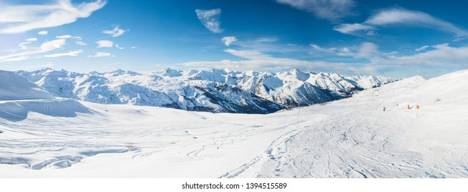 Panoramic view down snow covered valley in alpine mountain range on blue sky background
