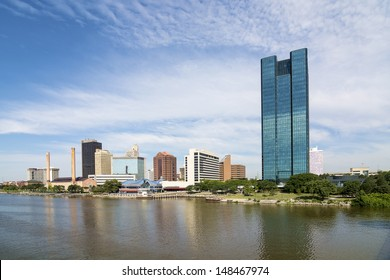 A panoramic view of downtown Toledo Ohio's skyline and the Maumee river.  A beautiful  blue sky with white clouds for a backdrop.