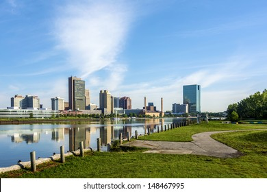 A panoramic view of downtown Toledo Ohio's skyline from across the Maumee river at a public park.  A beautiful  blue sky reflecting in the river.