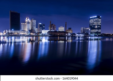 A panoramic view of downtown Toledo Ohio's skyline at night from across the Maumee river.  A beautiful  deep blue sky with the city lights reflecting into the Maumee river.