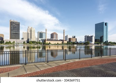 A  panoramic view of downtown Toledo Ohio's skyline from across the Maumee river at a popular restaurant area.  A beautiful  blue sky with white clouds for a backdrop.