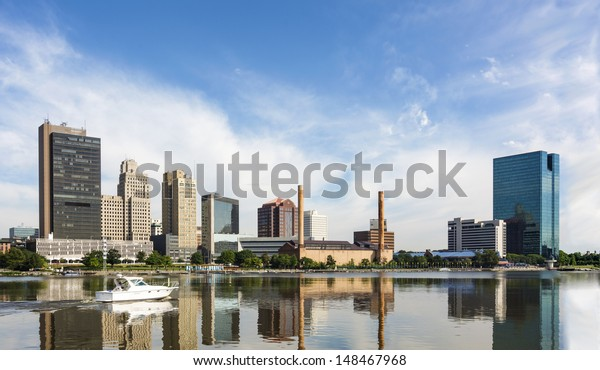 A panoramic view of downtown Toledo Ohio's skyline reflecting into the Maumee river with a power boat cruising by.  A beautiful  blue sky with white clouds for a backdrop.