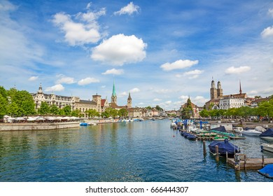 Panoramic view of downtown Zurich city center with famous Minsters called Grossmuenster and Fraumuenster and St. Peter church, river Limmat at Lake Zurich (Switzerland) in front, sunny day with clouds