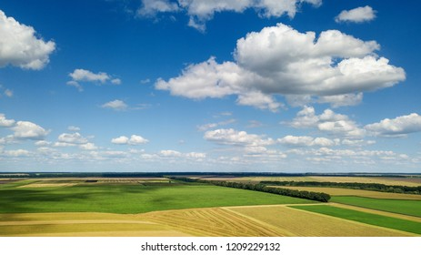 Panoramic view from the drone of beautiful landscape with greenery of trees, agricultural fields and meadows on the background of the cloudy sky at a summer day.
