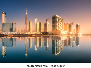 Panoramic view of Dubai Business bay with reflection of skyscrapers on water during sunrise, UAE