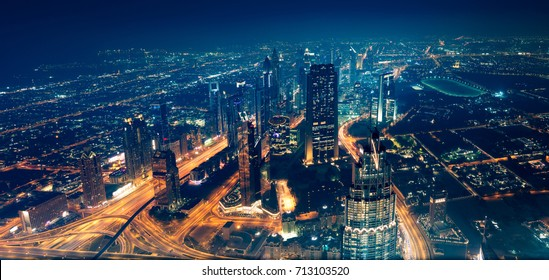 Panoramic view of Dubai city, beautiful modern new town at night with many bright glowing lights from the towers, magical place for traveling