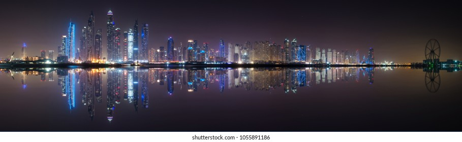 Panoramic view of Dubai Marina skyline with reflection at night, UAE