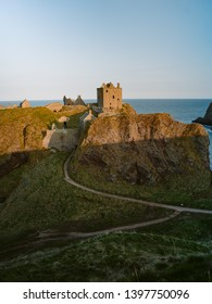 Panoramic view of Dunottar Castle at sunset on the East Coast of Scotland. Aberdeenshire, United Kingdom. Medieval fortress located upon a rocky headland on the north-east coast of Scotland