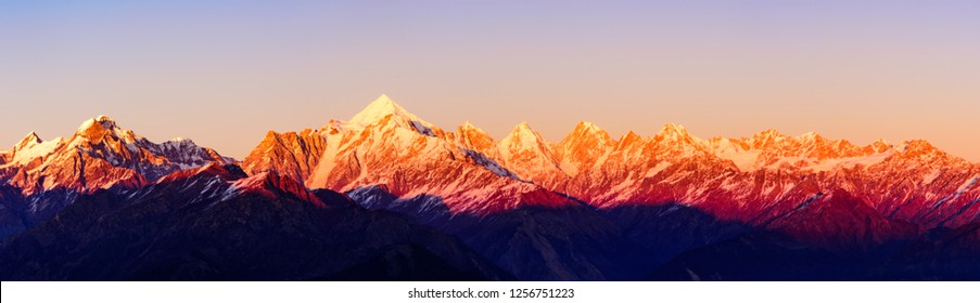 Panoramic view during sunset over snow cladded Panchchuli peaks falls in great Himalayan mountain range from small hamlet Munsiyari, Kumaon region, Uttarakhand, India.