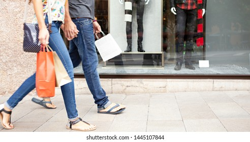 Panoramic view of dynamic couple walking together carrying bags and holding hands in shopping mall outdoors. Lower section faceless tourists consumers travel holiday, leisure recreation lifestyle.