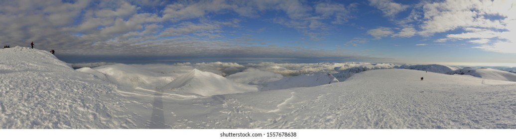 Panoramic view E of climbers and walkers on the summit of a snow clad Helvellyn (Lake District, England) on a glorious winter's day. Swirral Edge & Striding Edge are visible left & right of centre.