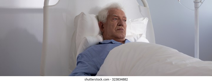 Panoramic view of elder man lying in hospital bed