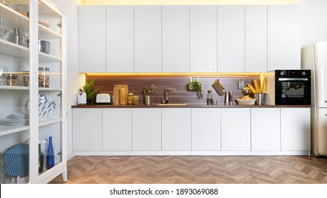 Panoramic view of elegant contemporary interior with white kitchen cupboards, wooden countertop, sink, electric oven, kitchenware in cabinet and utensil. Copy space on parquet or laminate floor