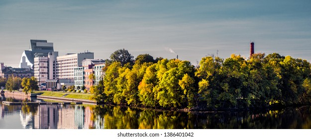 Panoramic view embankment of Riga city in autumn, lush trees reflected mirrored in Daugava River, blue sky copy space for text, sunny day. Latvia, Northern Europe