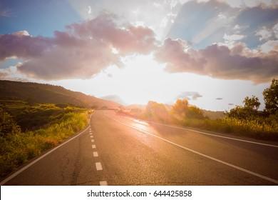 panoramic view of empty asphalt road under sunset sky, dusk light sunbeam, rural scene